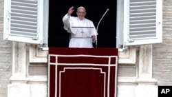 FILE - Pope Francis waves to the crowd as he arrives for the Angelus noon prayer from the window of his studio overlooking St. Peter's Square, at the Vatican, Feb. 25, 2018.
