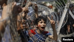 An Egyptian boy peers out of barbed wire during a protest in front of the Supreme Constitutional Court in Cairo, Egypt, Thursday June 14, 2012.