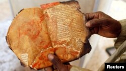 A museum guard displays a burned ancient manuscript at the Ahmed Baba Institute, or Ahmed Baba Center for Documentation and Research, in Timbuktu, Mali, Jan. 31, 2013.