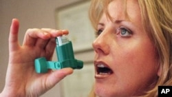 Registered nurse Darlene Martin, from Santa Monica, California, reaches for her asthma inhaler, March 1998. (file photo)