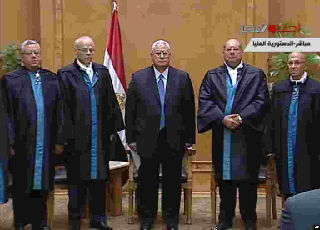 This image made from Egyptian State Television shows Egypt's interim president Adly Mansour, center, standing with judges during a swearing in ceremony in at the constitutional court in Cairo, July 4, 2013.