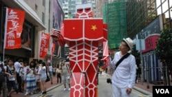 """黃國才2013年參與七一大遊行,他當年製作了一個概念來自日本漫畫、9呎高、全身紅色的""""進擊的共人""""紙製機械人, 代表一股很強大的、具有摧毀性的力量進擊香港(美國之音/湯惠芸)"""