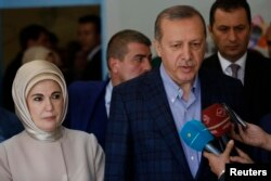 Turkish President Recep Tayyip Erdogan, accompanied by his wife Emine Erdogan, speaks to media after voting in Istanbul, Nov. 1, 2015.
