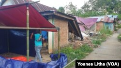 Seorang warga sedang mendirikan tenda terpal di depan rumahnya yang rusak akibat gempa di dusun Petakeang, Kecamatan Tapalang, Sulawesi Barat. Jumat (5/1/2021). (Foto: VOA/Yoanes Litha)