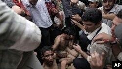 ພວກປະທ້ວງອີຈິບ ຈັບຜູ້ຊາຍປະມານ 30 ຄົນທີ່ມີມີດແລະໄມ້ຄ້ອນເປັນອາວຸດ ຊຶ່ງຈະພາກັນບຸກເຂົ້າໄປໃນ ບໍລິເວນຄ້າຍຕູບຜ້າຕັ້ງ ຂອງພວກປະທ້ວງ ທີຈະຕຸລັດ Tahrir ໃນກຸງໄຄໂຣ (12 ກໍລະກົດ 2011)