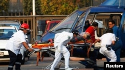 Paramedics wheel an injured person to a helicopter at the parking lot of the state-run oil company Pemex after an explosion in Mexico City, January 31, 2013.