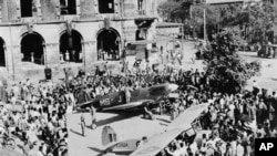 ဒုတိယကမၻာစစ္ၿပီးကာလ ရန္ကုန္ၿမိဳ႕မွာ ဆိုက္ကပ္ထားတဲ့ Spitfire ေလယာဥ္တခ်ိဳ႕ကို ၀ိုင္း၀န္း ၾကည့္ေနၾကပံု။ (ဧၿပီလ ၃ ရက္၊ ၁၉၄၆)။