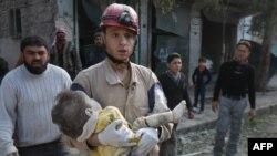 Seorang petugas pertahanan sipil menggendong mayat seorang anak yang terkena serangan udara di Aleppo, Suriah, Februari 2015. (AFP/AMC/Zein Al-Rifai)