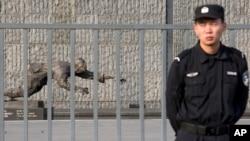 Bảo vệ đứng canh gác gần 1 tác phẩm điêu khắc miêu tả nạn nhân ở Nhà Tưởng niệm Thảm sát Nam Kinh, ở tỉnh Giang Tô phía đông Trung Quốc, trước buổi lễ đánh dấu 77 năm Thảm sát Nam Kinh, 12/12/2014.