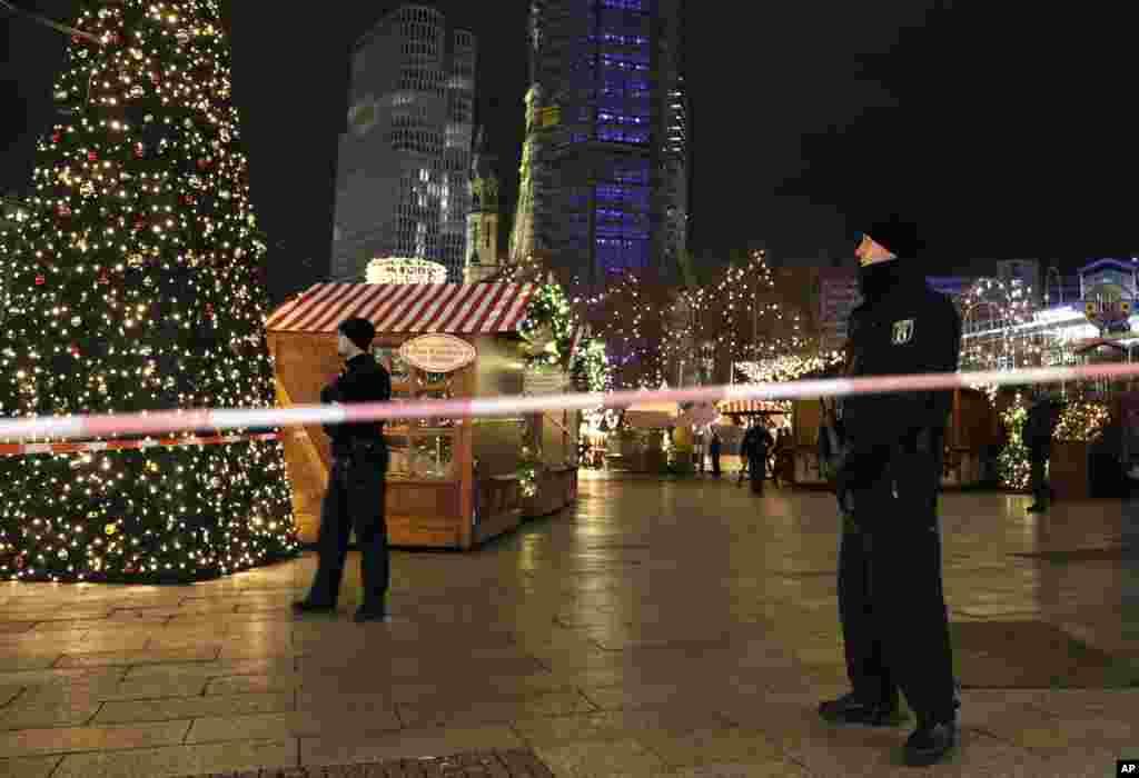 Polisi menjaga sebuah pasar Natal setelah truk sengaja menabrak kerumunan di pasar di Berlin, Jerman, itu. (AP/Michael Sohn)