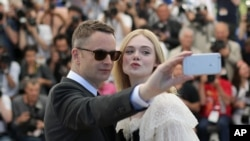 FILE - Director Nicolas Winding Refn and actress Elle Fanning pose for a selfie photograph during a photo call for the film The Neon Demon at the 69th international film festival, Cannes, southern France, Friday, May 20, 2016.