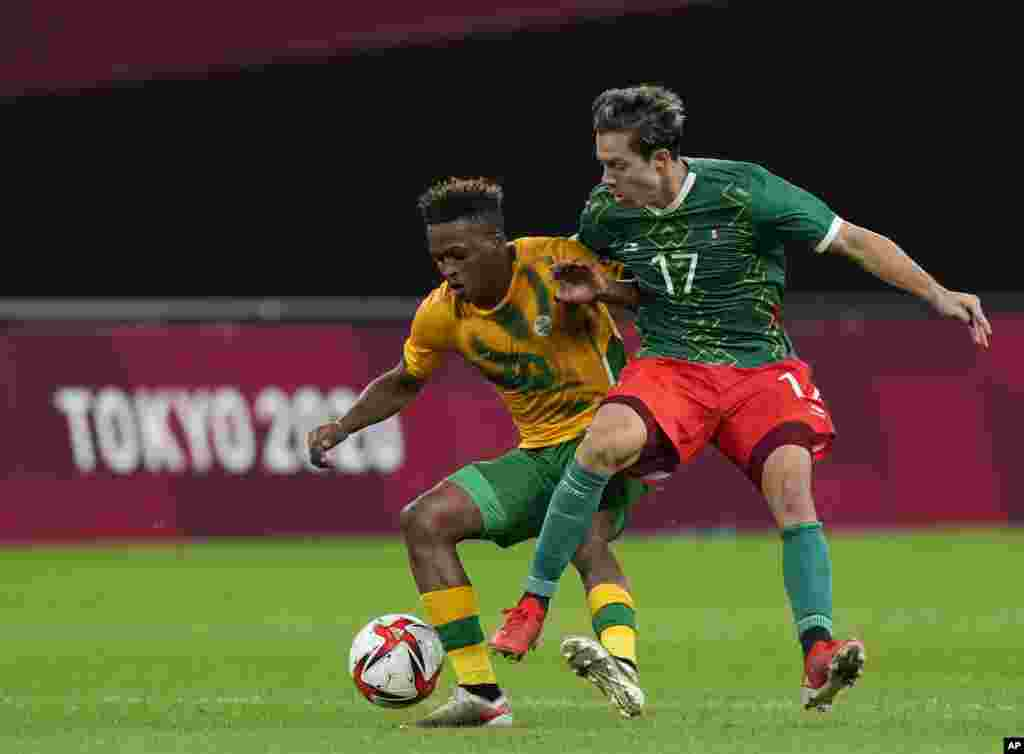 Luther Singh of South Africa, left, and Mexico's Sebastian Cordova fight for the ball during a men's soccer match at the 2020 Summer Olympics, Wednesday, July 28, 2021, in Sapporo, Japan. (AP Photo/Silvia Izquierdo)