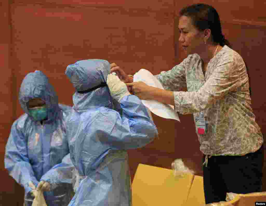 A Philippine health worker assists a colleague with protective suits and equipment during training at the Research Institute for Tropical Medicine hospital in Alabang, Muntinlupa, south of Manila, Oct. 28, 2014.