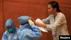 "FILE - A Philippine health worker assists a colleague with protective suits and equipment during the ""One Nation, One Direction for EBOLA Prevention"" training at the Research Institute for Tropical Medicine hospital in Alabang, Muntinlupa, south of Manila."