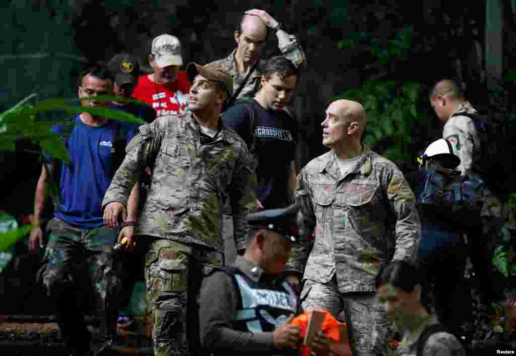 U.S. military personnel come out from Tham Luang cave complex during a search