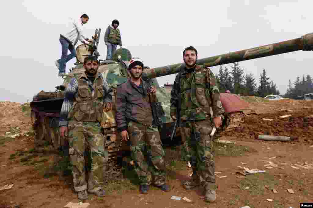 Free Syrian Army fighters pose with a tank after capturing the Military Infantry School following heavy clashes, Aleppo, Syria, December 16, 2012.