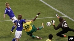 Japan's Keisuke Honda, top left, scores the opening goal against Cameroon goalkeeper Souleymanou Hamidou, right, and Cameroon's Stephane Mbia, third from left, during the World Cup group E soccer match between Japan and Cameroon at Free State Stadium in B