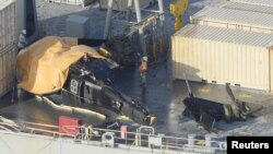 12일 일본 오키나와 해상에 추락한 미군 헬기가 미 해군함정에 실려있다.
