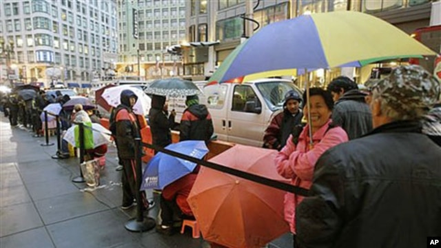 Apple customers use umbrellas as they wait in line at an Apple store on the first day of the launch of the new iPad, in San Francisco, March 16, 2012.