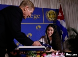 FILE - US Senator Bill Nelson (D-FL) presents a US flag to Yoani Sanchez, the best-known dissident blogger from Cuba, after she spoke at the Freedom Tower in Miami, Florida April 1, 2013.
