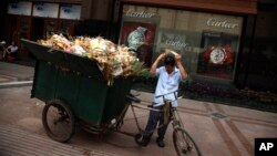 FILE - A man prepares to push a garbage cart near a shop selling luxury watches along a shopping street in Beijing, China, Aug. 3, 2010. Many of China's richest have embraced the philosophies of western capitalists who turned to philanthropy.