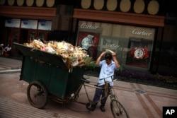 Ảnh tư liệu - Một người đàn ông chuẩn bị đẩy xe rác gần cửa hàng bán đồng hồ cao cấp dọc theo phố mua sắm ở Bắc Kinh, Trung Quốc, ngày 3 tháng 8 năm 2010.