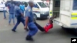 A South African man with his hands tethered to the back of a police vehicle being dragged behind as police hold his legs up and the vehicle apparently drives off, east of Johannesburg, Feb. 26, 2013. The man died of his injuries.