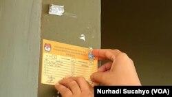 Seorang warga Sleman, DI Yogyakarta menempelkan stiker tanda akurasi data pemilih. Sleman menjadi salah satu kabupaten yang melaksanakan PIlkada 2020. (Foto: VOA/Nurhadi Sucahyo)
