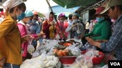 Garment factory workers wear face masks as they buy food on a lunch break near Propitious (Cambodia) Garment Ltd factory, in Kandal province, Cambodia, March 20, 2020. (Kann Vicheika/VOA Khmer)