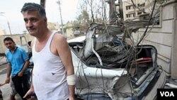 Warga Irak beragama Kristen berdiri dekat kendaraan yang hancur akibat serangan kawanan bersenjata di Baghdad, Minggu 31 Oktober 2010.