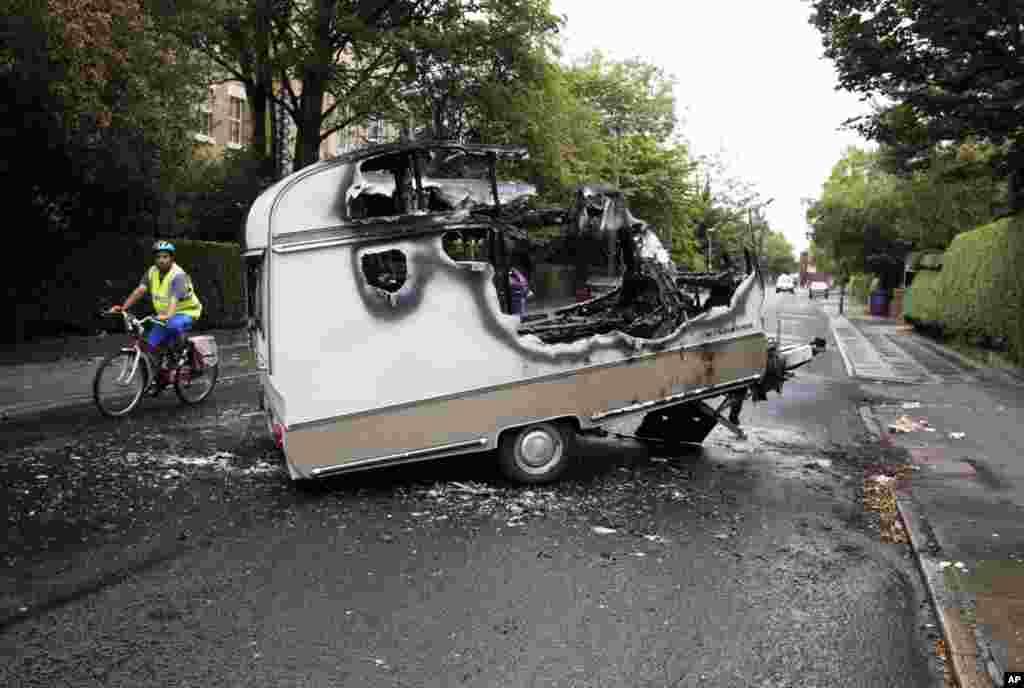 8月10日:在英格兰北部的利物浦,经过一整夜的暴乱和抢劫之后,一位骑自行车的人绕过一辆被焚毁的野营车。当地暴徒连续三个晚上到处抢劫和放火。英国城市从星期三开始清理一片狼籍的街道。(REUTERS/Phil Noble)