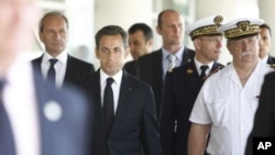 France's President Nicolas Sarkozy (C) and Defense Minister Gerard Longuet (L) leave the Percy hospital in Clamart, neat Paris after visiting French soldiers wounded in Afghanistan, July 14, 2011