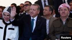 Turkey's Prime Minister Tayyip Erdogan and President of Iraqi Kurdistan Masoud Barzani (R) attend a ceremony with Erdogan's wife Emine Erdogan in Diyarbakir, Turkey, Nov. 16, 2013.