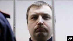 Mikhail Kosenko berdiri di balik jeruji saat disidang di Moskow (8/10). Kosenko merupakan salah satu dari 28 orang yang ditangkap setelah bentrokan pecah antara demonstran dan polisi dalam protes 6 Mei 2012, menjelang pelantikan Presiden Vladimir Putin untuk masa jabatan ketiga.