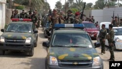 Iraqi police and soldiers parade in the city of Ramadi, the capital of Iraq's Anbar province, west of Baghdad on March 29, 2014 after they reportedly seized vehicles from militant fighters.