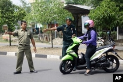 Police in Aceh direct a woman on a motor bike (AP)