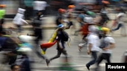 FILE - Demonstrators run during clashes with riot security forces at a protest against Venezuelan President Nicolas Maduro's government in Caracas, Venezuela, May 30, 2017.