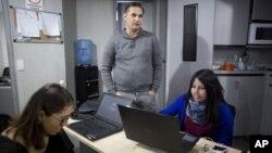 En esta imagen, tomada el 16 de octubre de 2018, César Batiz, director de El Pitazo (centro), junto a dos periodistas en la redacción de la popular plataforma digital en Caracas, Venezuela.