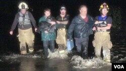 Petugas penyelamat membantu beberapa warga yang terjebak banjir akibat badai Irene di kota Montpelier, Vermont (28/8).