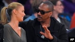 Actor Eddie Murphy talks with his girlfriend Paige Butcher during an NBA basketball game between the Los Angeles Lakers and the Dallas Mavericks, April 12, 2015, in Los Angeles.