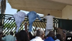 Unidentified lawmakers scale the parliament gate, in Abuja, Nigeria. Nov. 20, 2014.
