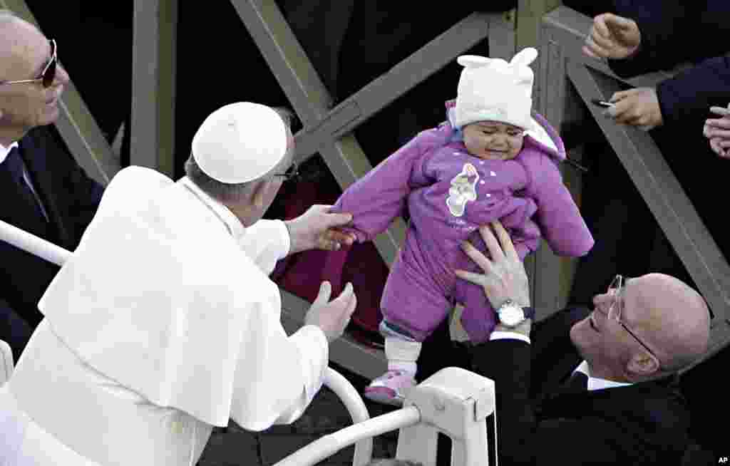 Pope Francis reaches out for a child in Saint Peter's Square at the Vatican, March 19, 2013.