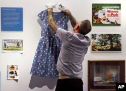 """A gallery stylist hangs a dress, fashioned with polka dots and Winnie the Pooh characters, while preparing a display at the """"Winnie-the-Pooh: Exploring a Classic"""" exhibit at the Museum of Fine Arts in Boston, Sept. 13, 2018."""