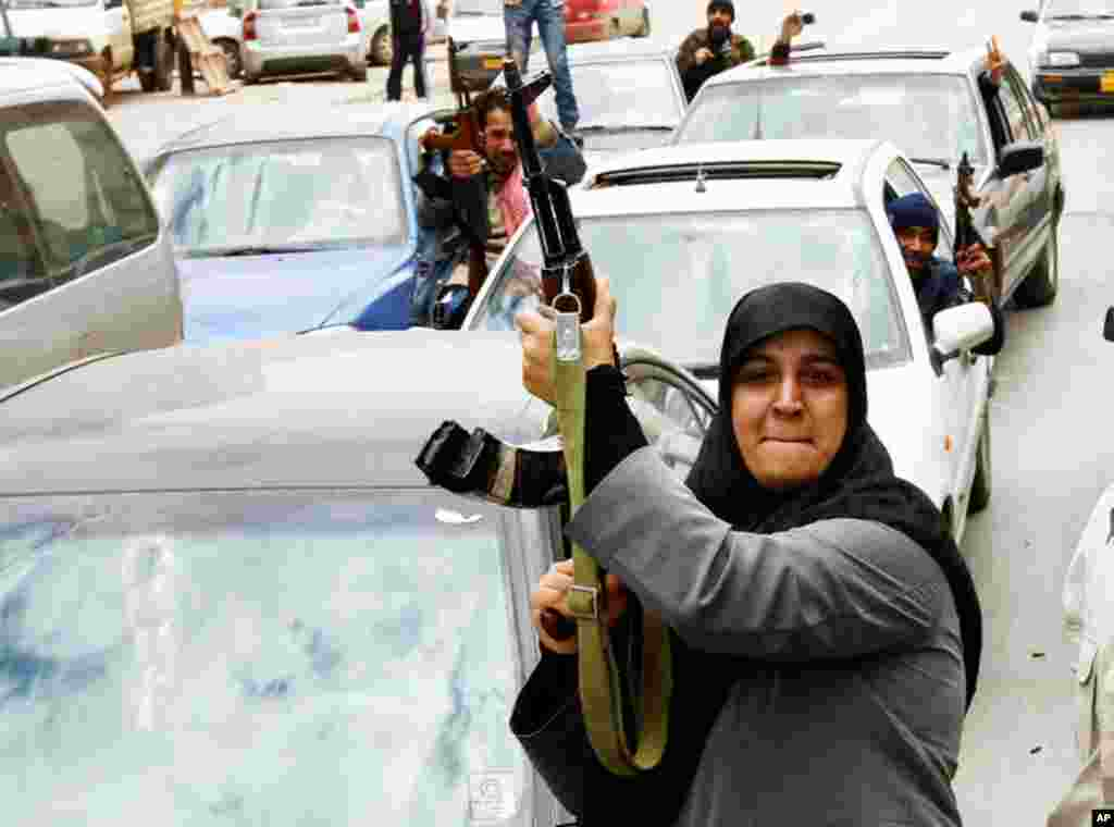 A rebel fighter supporter shoots an AK-47 rifle as she reacts to the news of the withdrawal of Libyan leader Muammar Gadhafi's forces from Benghazi, March 20, 2011. (Reuters/Goran Tomasevic)
