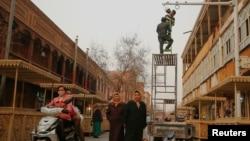 2017年3月23日工作人員在中國新疆維吾爾自治區喀什老城區購物街上安裝相機。