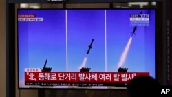 People watch a TV screen airing reports about North Korea's firing missiles with file images of missiles at the Seoul Railway Station in Seoul, South Korea, April 14, 2020.
