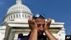 """A Capitol Hill police officer wipes sweat from his eyes as he stands his post on the West side of Capitol Hill in Washington, D.C., July 20, 2019. The National Weather Service said """"a dangerous heat wave"""" was expected to break record highs in some places."""