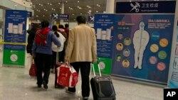 Calon penumpang melewati pos pemeriksaan kesehatan sebelum memasukin pemeriksaan imigrasi di Bandara International Beijing, China, 13 Januari 2020.