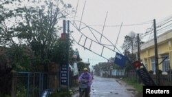 A man bikes past a broken sign as the Typhoon Molave lashes Vietnam's coast in Binh Chau village, Quang Ngai province, Oct. 28, 2020.