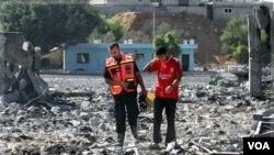 Warga Palestina sedang memeriksa kerusakan yang timbul di tempat pelatihan Hamas setelah serangan udara Israel di Gaza (21/8).